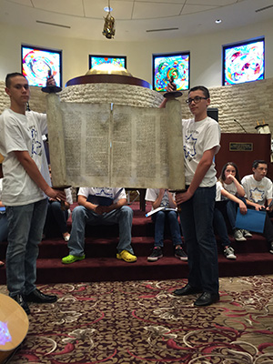 Hebrew School students unrolling a Czech Scroll at our Yom Hashoah Commemoration Ceremony.